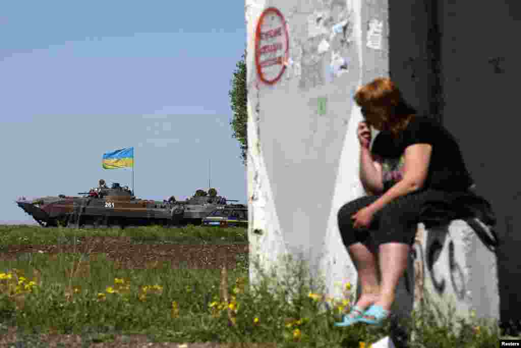 A woman looks at a Ukrainian armored personnel carrier at a checkpoint, in Mariupol, May 7, 2014.
