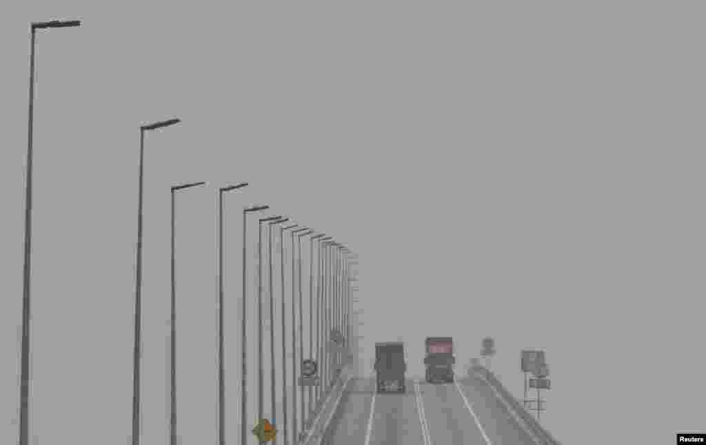 "Trucks cross a bridge shrouded in haze in Klang, Malaysia. The thick so-called ""haze,"" caused by slash-and-burn clearances on the islands of Sumatra and Borneo, has pushed air quality to unhealthy levels in Malaysia and neighboring Singapore."