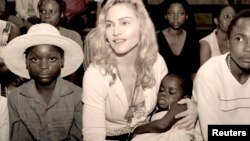 Pop star Madonna holds her adopted child, Mercy, undated publicity photo, Malawi, released April 13, 2009.