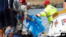 Water safety officials hand over possible debris from an Army UH-60 Black Hawk helicopter crash to military personnel stationed at a command center in a harbor, Aug. 16, 2017 in Haleiwa, Hawaii. An Army helicopter with five on board crashed several miles off Oahu's North Shore, Aug. 15, 2017. Tuesday.