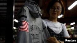 Một công nhân với chiếc áo khoác của Nike cho đội tuyển Olympic Mỹ do công ty may mặc Maxport sản xuất tại Việt Nam. Các lãnh đạo ngành may mặc và giày dép Mỹ kêu gọi Tổng thống Biden tăng tốc viện trợ vaccine cho Việt Nam vì lo ngại chuỗi cung ứng bị đứt gãy vì COVID.