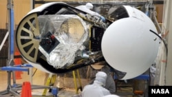 An Orbital Sciences technician completes final checks of NASA's Nuclear Spectroscopic Telescope Array, or NuSTAR