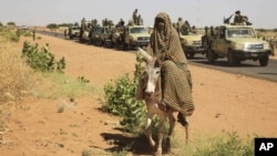 A government convoy passes a woman on a donkey in Tabit in North Darfur on Nov. 20, 2014. Human Rights Watch says Sudanese forces raped scores of women in the village last year. (AP/Abd Raouf)
