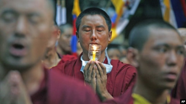 Tibetan monks pray during a candlelight protest march, saying harsh Chinese control pushes Tibetans into setting themselves on fire, in New Delhi, India, October 20, 2011.
