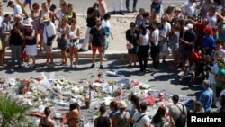 People form a circle around flowers placed on the road in tribute to victims of the truck attack along the Promenade des Anglais on Bastille Day that killed scores and injured as many in Nice, France, July 17, 2016.