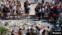 Người dân đứng quanh khu vực đặt hoa tưởng niệm các nạn nhân thiệt mạng trong vụ tấn công khủng bố ở Nice tuần trước, Pháp, ngày 17/7/2016.
