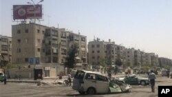Seorang warga berjalan melewati mobil yang rusak pasca bentrokan antara pemberontak dan pasukan Suriah di tempat penampungan pengungsi Palestina Yarmouk di selatan Damaskus (Foto: dok). Dilaporkan tbentroka kembali pecah di wilayah ini, Selasa (18/12).