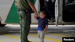 Un agente de la patrulla fronteriza de EE. UU. toma de la mano a un niño que ha entrado irregularmente en el país, en este caso, acompañado de su madre, en busca de asilo, el 15 de marzo de 2021.
