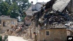 在意大利中部山地农业地区的灾区,一位军人走过瓦砾(2016年8月27日)