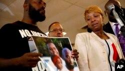 密蘇里州被警察打死的黑人青年的母親(右)與手拿家庭照片的父親(左)。18歲的邁克爾布朗在照片的左上角。