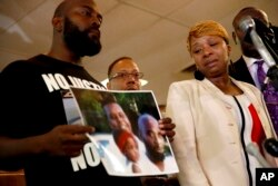Michael Brown'ın fotoğrafını tutan anne ve babası