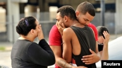 Friends and family members embrace outside the Orlando Police Headquarters during the investigation of a shooting at the Pulse night club in Orlando, Florida, June 12, 2016. REUTERS/Steve Nesius