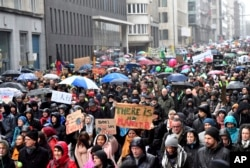 """Protesters hold banners as they march during a """"Rise for the Climate"""" demonstration in Brussels, Belgium, Jan. 27, 2019."""