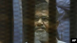 FILE - Egypt's ousted president Mohammed Morsi is seen sitting in a cage inside a makeshift courtroom at Egypt's national police academy in Cairo, Egypt, Apr. 21, 2015.