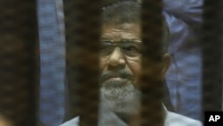 FILE - Egypt's ousted Islamist President Mohammed Morsi sits in a soundproof glass cage inside a makeshift courtroom at Egypt's national police academy in Cairo, Egypt, April 21, 2015.