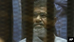 Egypt's ousted Islamist President Mohammed Morsi sits in a soundproof glass cage in a makeshift courtroom at the national police academy in Cairo, April 21, 2015.