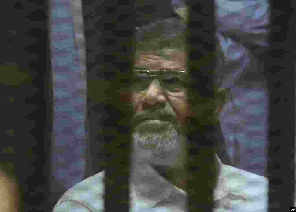 Presiden terguling Mohammed Morsi duduk di sel kaca kedap suara dalam pengadilan darurat di akademi polisi nasional Mesir di Kairo (21/4). (AP/Amr Nabil)