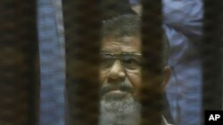 FILE - Egypt's ousted Islamist President Mohammed Morsi sits in a soundproof glass cage inside a makeshift courtroom at Egypt's national police academy in Cairo, April 21, 2015.