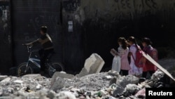 Children go to school on a damaged street in Damascus.