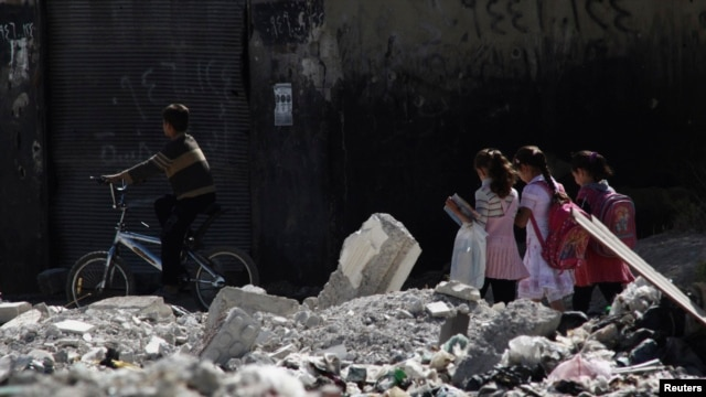 Children go to school on a damaged street in  Damascus.
