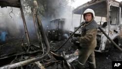 Donetsk'de top ateşinin ardınan yanan otobüsleri söndürmeye çalışan itfaiyeciler