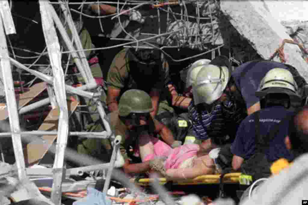 Rescue workers help an injured woman in Concepcion, 500 km south of Santiago, 27 Feb 2010