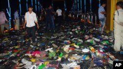 Cambodians walk through piles of shoes on a newly-built bridge where the worst stampede in their country's modern history happened, killing at least 345 people on Monday, November 22, 2010.