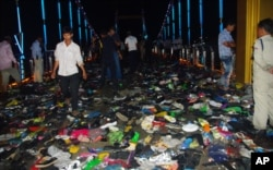 FILE - Cambodians walk through piles of shoes on a newly-built bridge where the worst stampede in their country's modern history happened, killing at least 345 people on Monday, November 22, 2010.