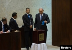 Israel's Prime Minister Benjamin Netanyahu, right, casts his ballot for the presidential election at the Knesset, Israel's parliament, in Jerusalem, June 10, 2014.