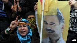 A person holds a poster of jailed Kurdish rebel leader Abdullah Ocalan as Kurdish demonstrators march in Istanbul, Turkey, April 19, 2011.