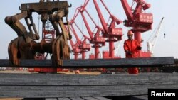 A worker loads steel bars for export at a port in Lianyungang, Jiangsu province Jun. 4, 2013.