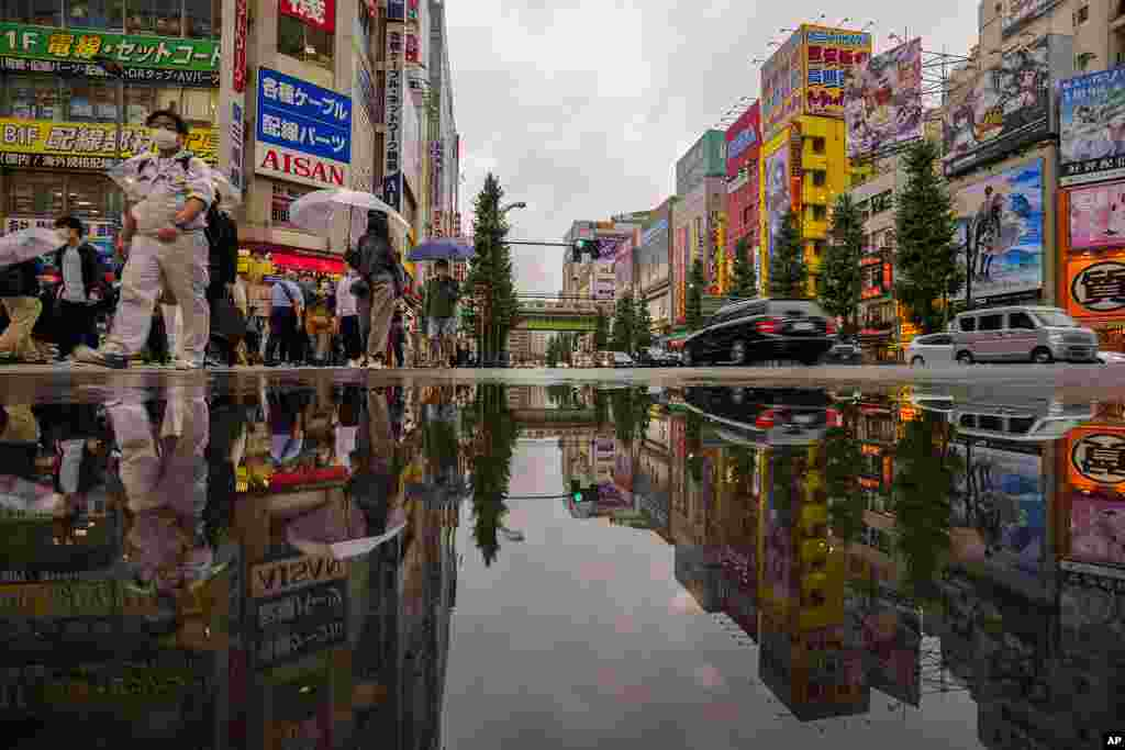 People wearing protective masks are reflected in a puddle as they walk across a street in a shopping district in Tokyo. Japan fully came out of a coronavirus state of emergency for the first time in more than six months on October 1.