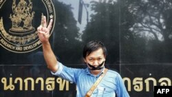 FILE - Thai journalist Pravit Rojanaphruk flashes a V-sign as he stands with his mouth taped outside a military base in Bangkok where he had been summoned by the junta, May 25, 2014.