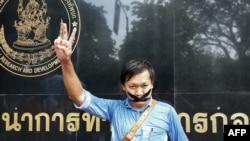"""Wartawan Thailand Pravit Rojanaphruk memberikan tanda """"V"""" dengan mulut yang ditutup isolasi di luar markas besar militer di Bangkok, 25 Mei 2014 (Foto: dok)."""