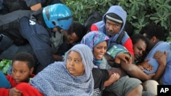 Des policiers Police in Ventimiglia, Italy drag Eritrean and Sudanese refugees from encampments near the French border last June. Paris officials refused to let them cross into France.