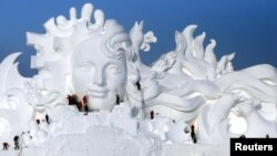 2016年12月13日艺术家在中国黑龙江省哈尔滨展览会上展出雪雕