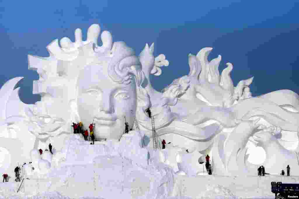 Artists work on snow sculptures at an exhibition in Harbin, Heilongjiang province, China.