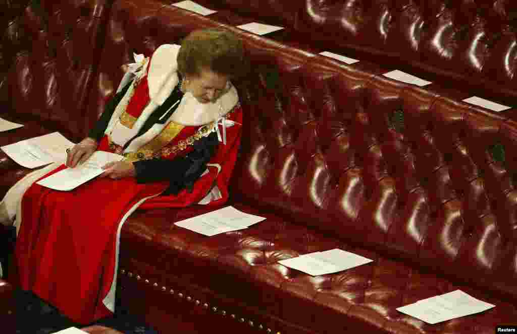 Britain's Baroness Thatcher read the order of service surrounded by empty seats as she waited for Queen Elizabeth to deliver her speech at the State Opening of Parliament in the House of Lords, Nov. 13, 2002.