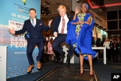 FILE - Britain's Prime Minister Boris Johnson, center, visits the Pavegen stand, a company that converts footsteps into energy, at the Innovation Zone during the UK Africa Investment Summit in London, Jan. 20, 2020.