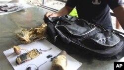 Seorang polisi Filipina memerikas bom rakitan (IED) yang ditemukan berada di dalam ransel milik warga Malaysia anggota Jemaah Islamiyah, Sabtu (15/12). Tersangka teroris bernama Mohamad Nur Fikri Bin Abu Kahar, ditembak mati polisi setempat setelah yang bersangkutan berusaha meledakkan bom tersebut di kota Davoa, Jum'at (14/12).