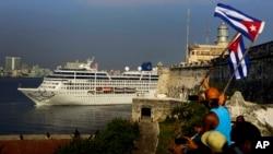Des habitants font voler un drapeau cubain dans les airs, saluant l'arrivée des passagers de la croisière.