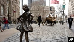 "A statue titled ""Fearless Girl"" faces the Wall Street bull, March 8, 2017, in New York. A big investment firm, State Street Global Advisors, put the statue there to highlight International Women's Day. The work by artist Kristen Visbal."