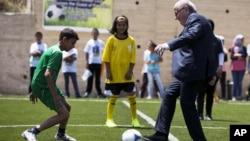 FILE: FIFA President Sepp Blatter kicks a ball during the inauguration of a football stadium in the village of Dura Al-Qari' near the West Bank city of Ramallah, May 20, 2015.