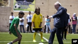 FILE - FIFA President Sepp Blatter kicks a ball during the inauguration of a football stadium in the village of Dura Al-Qari' near the West Bank city of Ramallah, May 20, 2015.