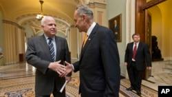 El senador John McCain (izq.) y su par demócrata Charles Schumer, parte del Grupo de los Ocho, celebran la aprobación de una reforma migratoria.