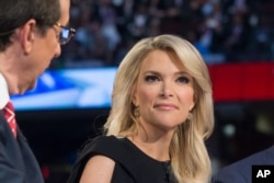 FOX News moderators Megyn Kelly, right, listens as Chris Wallace beings introductions during the first Republican presidential debate at the Quicken Loans Arena, Aug. 6, 2015, in Cleveland.