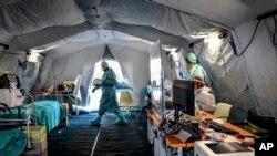 Le personnel médical à l'intérieur d'une des structures d'urgence qui ont été mises en place pour faciliter les procédures à l'extérieur de l'hôpital de Brescia, en Italie, le mardi 10 mars 2020. (Claudio Furlan/LaPresse via AP)
