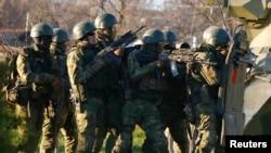Pria-pria bersenjata, diyakini merupakan tentara Rusia, berlindung di balik tank saat berupaya merebut pangkalan angkatan udara di Belbek, Krimea (22/3).