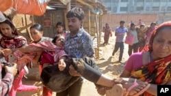 Para pekerja gamen Bangladesh membantu rekannya yang luka saat terjadi bentrokan dengan polisi di Ashulia, luar Dhaka, Bangladesh (12/11).