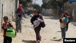 Warga Palestina melarikan diri dari rumah mereka sewaktu tank Israel menggempur kota Rafah di Jalur Gaza 1 Agustus 2014.